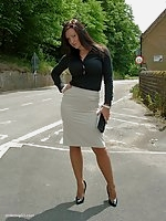 Sexy brunette in a tight skirt, with long stockinged legs and shiny black stilettos